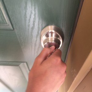 hand turning key in door
